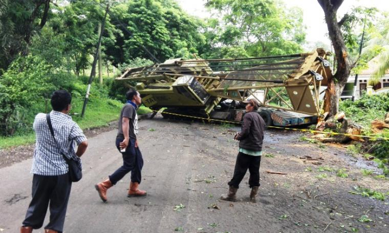 Truk trailer membawa crane terguling saat tak mampu melaju ditanjakan. (Foto:TitikNOL)