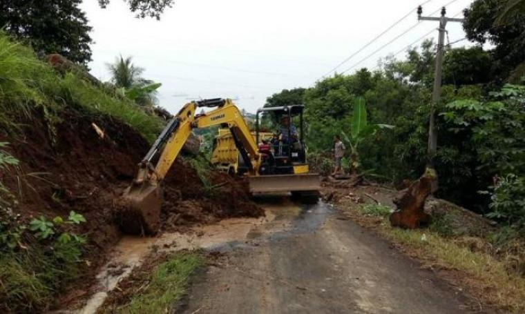 Kendaraan berat saat mengeruk tanah yang menutup jalan akibat longsor. (Foto:TitikNOL)