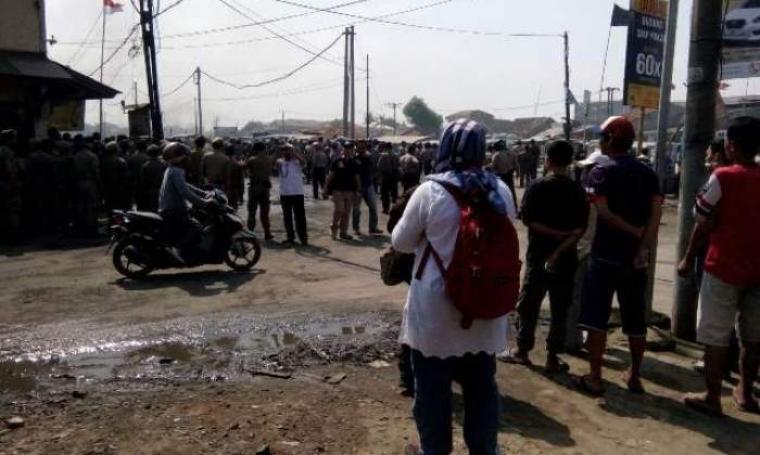 Suasana bentrokan antara aparat kepolisian dan warga yang disaksikan sejumlah pengguna jalan dan warga lainnya saat proses penertiban lokalisasi. (Foto:TitikNOL)