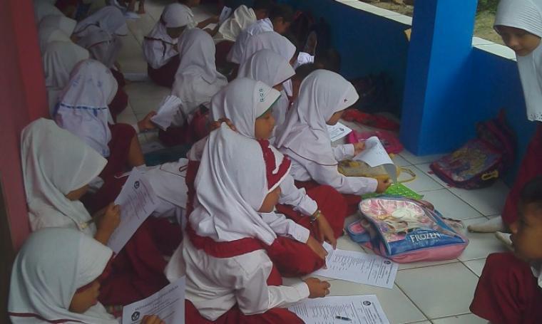 Sejumlah murid SD saat mengerjakan pelaksanaan Ujian Akhir Semester di luar ruang kelas. (Foto:TitikNOL)