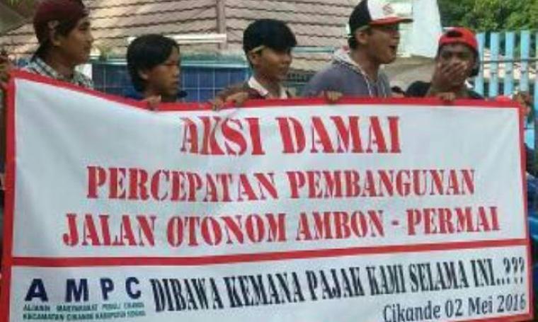 Sejumlah warga saat memblokir jalan dengan menggunakan spanduk dengan bentuk kekesalan atas kondisi jalan yang rusak parah. (Foto:TitikNOL)