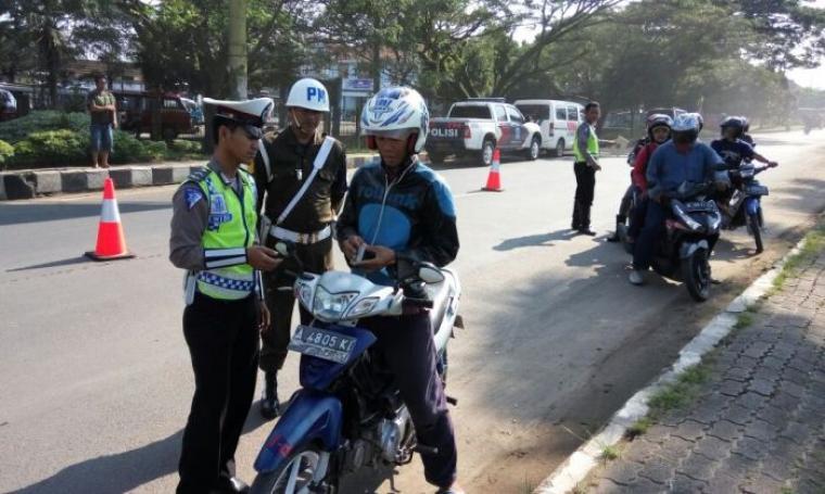 Petugas gabungan Satlantas Polres Lebak dan Polisi Militer, saat gelar operasi Patuh Kalimaya 2016 di Jalan Raya Ahmad Yadi, Mandala, Rangkasbitung, Kabupaten Lebak. (Foto:TitikNOL)