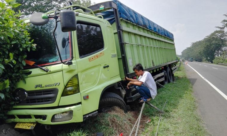 Kondisi truk fuso yang terperosok di pembatas jalan Tol. (Foto: TitikNOL)