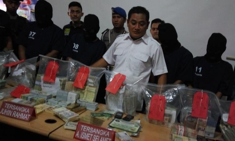 Dirkrimum Polda Banten, Kombes Pol Yusfadillah (tengah) menghadirkan keempat tersangka pengedar ratusan jenis uang palsu dan sejumlah barang bukti saat pers conference. (Foto: TitikNOL)