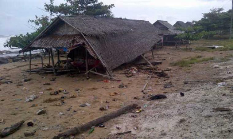 Sebuah warung di Pantai Pasir Putih, Desa Ciparahu nyaris roboh akibat terkena ombak. Sebelumnya di lokasi ini banyak warung, namun kini hilang tersapu ombak. (Foto: TitikNOL)