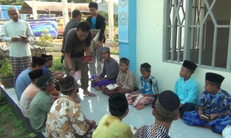 Salah satu relawan saat memberikan Al-Quran ke sejumlah santri. (Foto: TitikNOL)