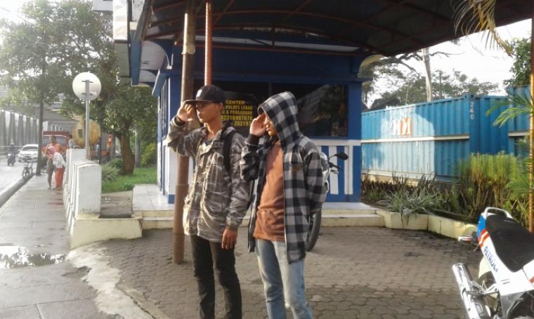 Kedua pengendara saat melakukan sanksi dari petugas Polantas Polres Lebak untuk memberi hormat kepada pengguna jalan yang melintas. (Foto: TitikNOL)