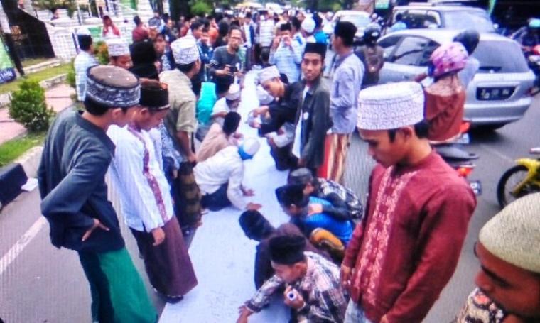 Ratusan ulama dan santri saat melekukan aksi dengan membubuhkan tanda tangan. (Foto: TitikNOL)