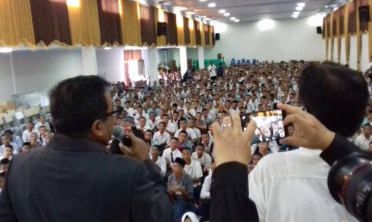 Gubernur Banten, Rano Karno (membelakangi kamera, baju hitam) saat memberikan sambutan di depan ribuan siswa SMKN 2 Kota Serang. (Foto: TitikNOL)