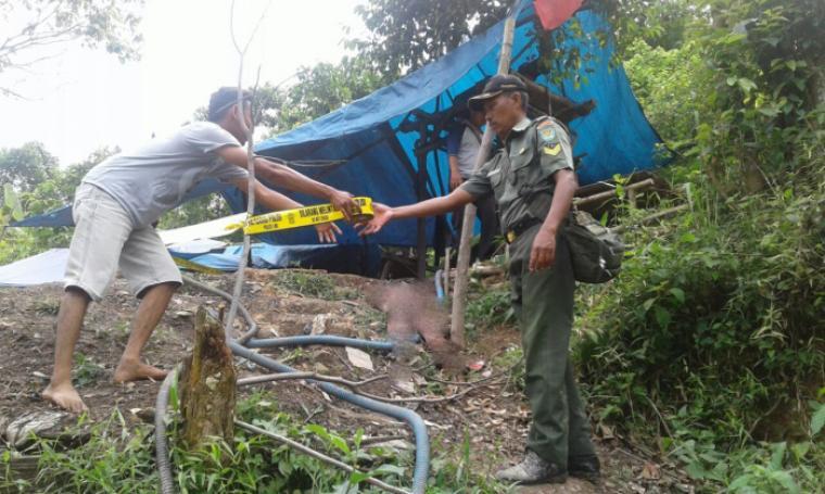 Dua orang petugas saat memasang garis polisi di lokasi ditemukannya mayat. (Foto: TitikNOL)