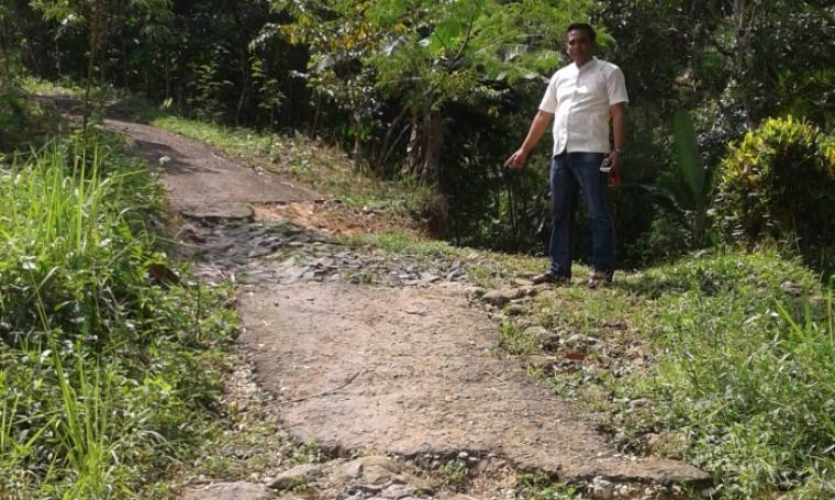 Alek, Kades Cijengkol saat menunjukan lokasi jalan poros desa yang rusak parah. (Foto: TitikNOL)