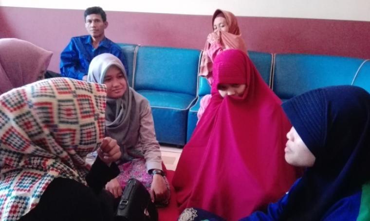 Qonita Nur Ulfah (kerudung merah) dikunjungi teman-temannya saat berada di Mapolres Cilegon. (Foto: TitikNOL)