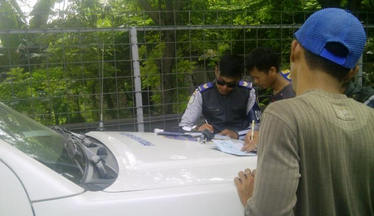 Seorang petugas Dishubkominfo Banten saat sedang mencatat surat tilang dua sopir angkot di Kota Serang. (Foto:TitikNOL)