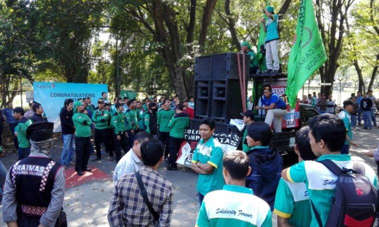 Suasana aksi unjuk rasa buruh yang dijaga ketat pihak kepolisian Polres Cilegon di depan pintu masuk PT Cabot Indonesia, Kota Cilegon, Kamis (28/7/2016). (Foto: TitikNOL)