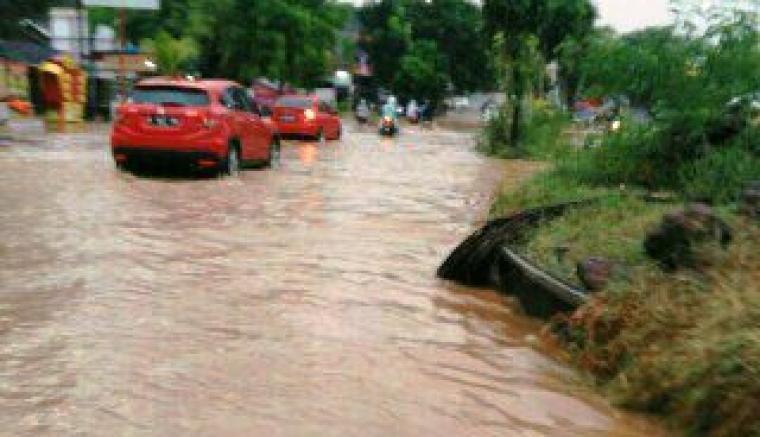 Kendaraan roda empat saat melintas di jalur perumahan Argabaja Pura, Kota Cilegon yang terendam banjir. (Foto:TitikNOL)