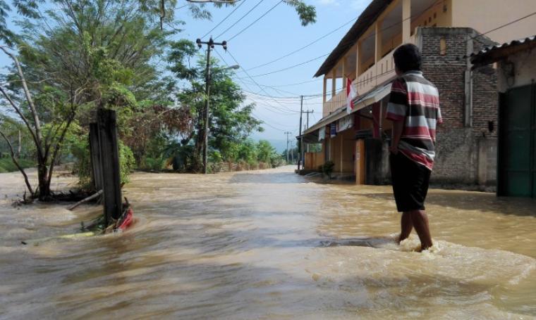 Warga berusaha menembus genangan air di Kelurahan Gedong Dalem,Kecamatan Jombang,Kota Cilegon. (Foto: TitikNOL)