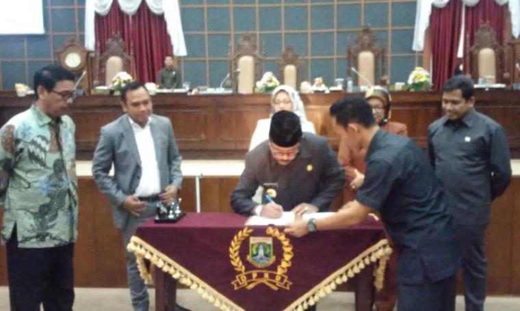 Gubernur Banten Rano Karno saat menandatangani berita acara pengesahan raperda APBD Perubahan TA 2016 Provinsi Banten, dalam paripurna di DPRD Banten, KP3B, Kota Serang, Jumat (30/9/2016). (Foto: Titi