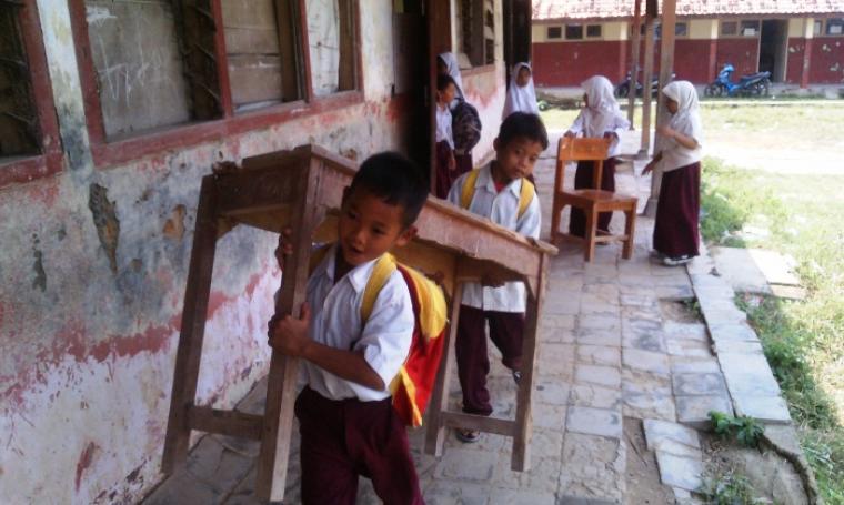 Sejumlah siswa di SDN Sampang menggotong bangku dari ruang kelas yang rusak ke ruang kelas lainnya yang masih layak, untuk persiapan proses belajar mengajar. (Dok:TitikNOL)