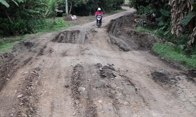 Salah satu pengendara motor saat melintasi jalan bergelombang yang diduga rusak akibat lalu lalangnya kendaraan dump truck pengangkut material batu. (Foto: TitikNOL)
