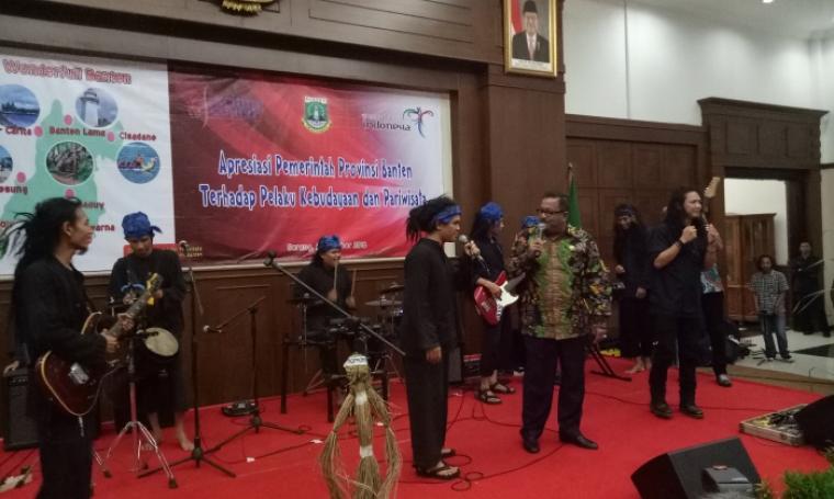 Gubernur Banten Rano Karno tengah menyanyikan lagu SI Doel Anak Sekolahan bersama grup band Momonon. (Foto: TitikNOL)