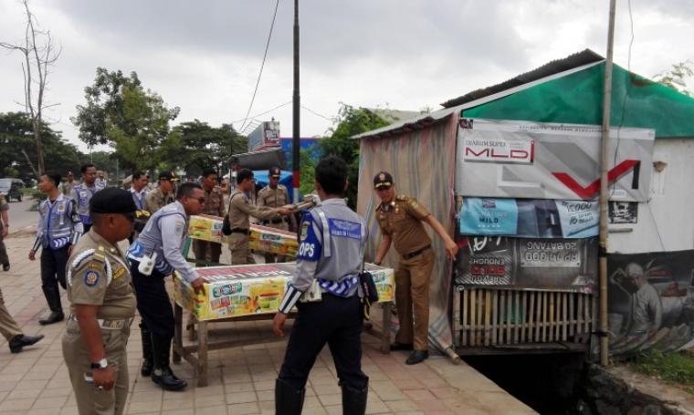 Petugas Dishub dan Satpol PP Kota Cilegon tengah menertibkan lapak PKL yang berjualan di sekitar trotoar Jalan Lingkar Selatan. (Foto: TitikNOL)