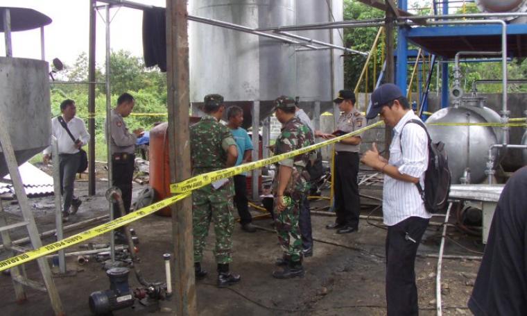Sejumlah petugas dari Polsek Rangkasbitung memasang garis pembatas Police Line di lokasi ledakan tabung minyak milik pabrik produsen Karbon PT Tanso Putera Asia. (Foto: TitikNOL)