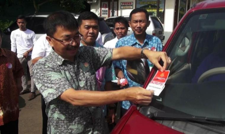 Wakil Kajati Banten Jaya Kusuma saat memasang stiker bergambar perlawanan terhadap korupsi kepada pengguna kendaraan roda empat. (Foto: TitikNOL)