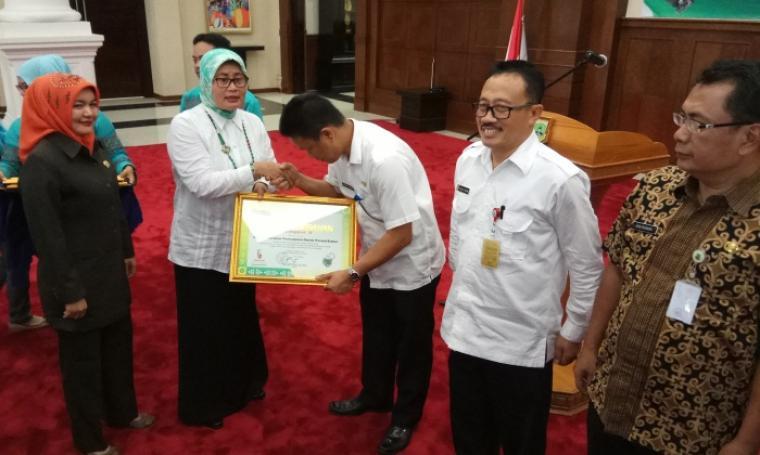 Asda II Pemprov Banten Eneng Nurcahyati memberikan penghargaan terhadap badan publik dalam penganugerahan pemeringkatan KIP, di Pendopo Gubernur, KP3B, Kota Serang. (Foto: TitikNOL)