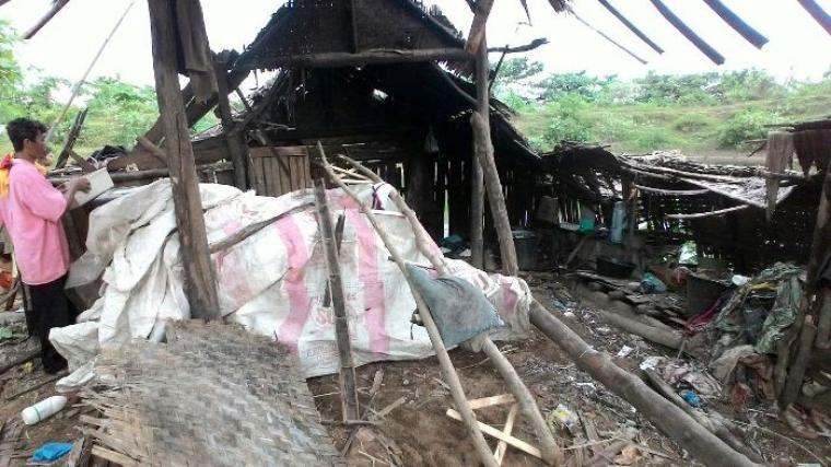 Madasim (berbaju merah muda), saat membereskan barang-barang di puing rumahnya yang roboh. (Foto:TitikNOL)