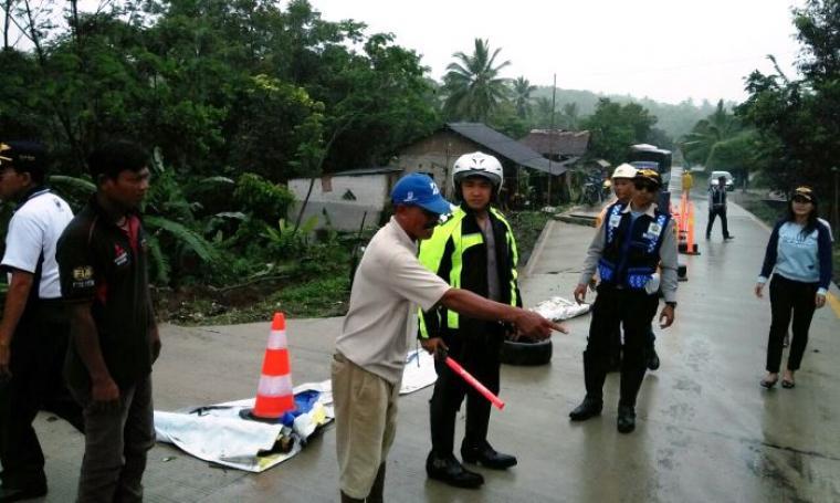Anggota Polisi dari Polres Lebak turut melakukan kegiatan pengaturan, pengalihan arus lalu lintas dan pendampingan di jalan Saketi-Malingping yang mengalami amblas. (Foto: TitikNOL)