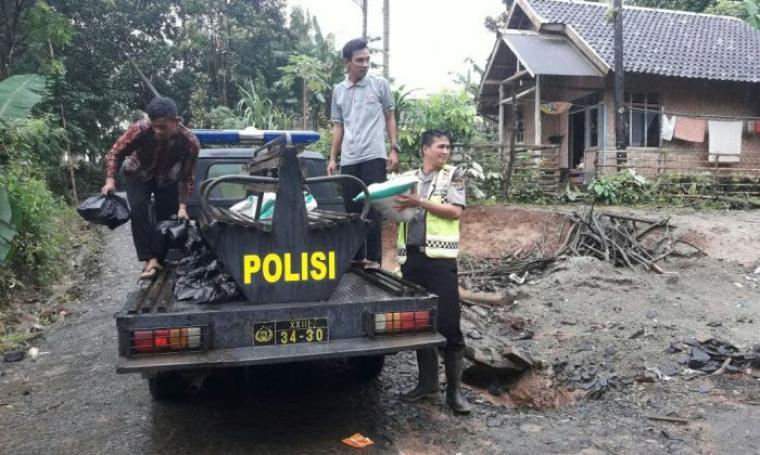 Salah satu anggota dari Polres Lebak saat memberikan bantuan berupa sembako dan air mineral kepada korban banjir. (Foto: TitikNOL)