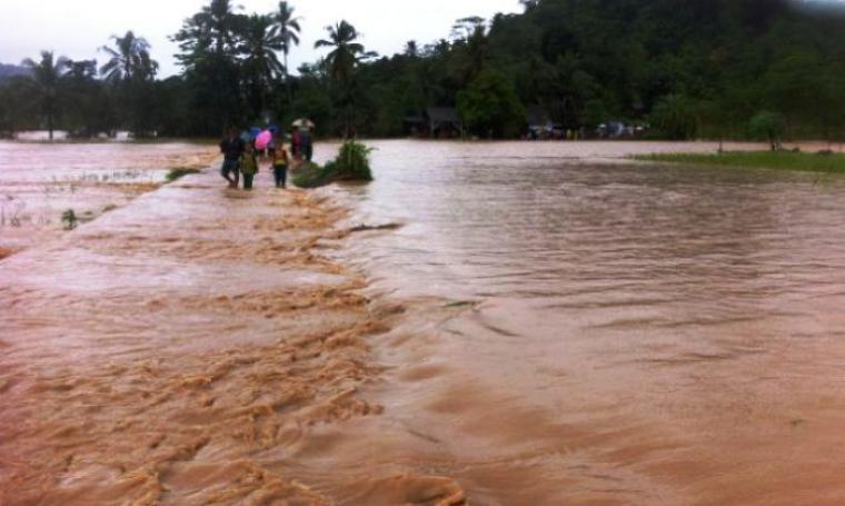 Warga saat melintasi banjir yang menggenangi jalan dan sawah di kampung Cimancak, Kecamatan Bayah, Kabupaten Lebak. (Foto: TitikNOL)