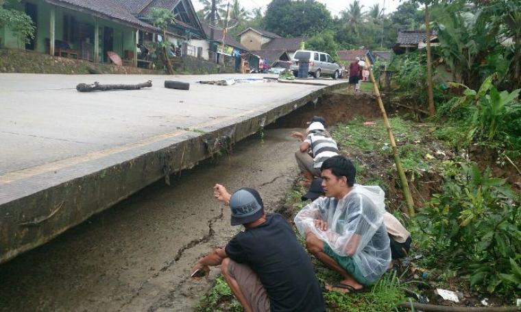 Warga tengah melihat-lihat kondisi tanah yang amblas dibawah kolong ruas jalan nasional Saketi - Malingping. (Foto: TitikNOL)