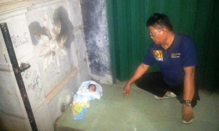 Petugas Polsek Cinangka saat akan memberikan pertolongan kepada bayi yang dibuang. (Foto: Istimewa)