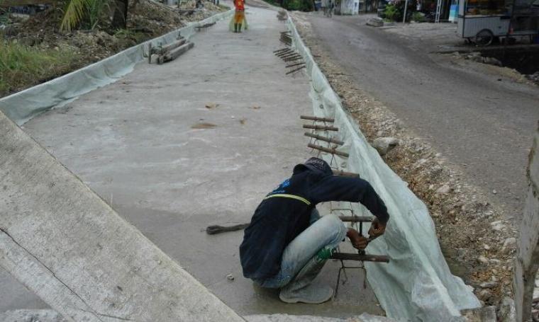 Seorang pekerja sedang memasang besi di pembanguanan proyek pengerjaan jalan nasional Bayah - Cibareno. (Foto: TitikNOL)