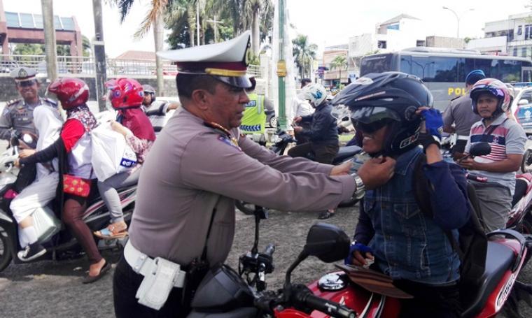 Petugas Satlantas Polres Cilegon membantu mengenakan helm yang benar kepada salah satu pengendara sepeda motor dalam operasi Simpatik 2017 di Kawasan Bonakarta Cilegon. (Foto: TitikNOL)