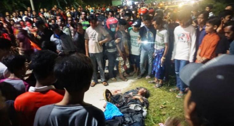 Ratusan warga berkerumun menyaksikan pria hanas yang tergolek lemas usai dihakimi beramai-ramai. (Foto: TitikNOL)
