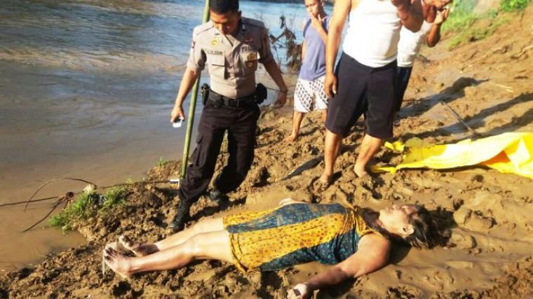 Anggota polisi dibantu warga, saat mengevakuasi jasad korban dari Sungai Cisimeut. (Foto: Ist)