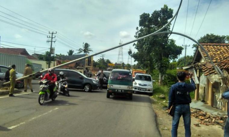 Kondisi Lampu Penerang Jalan Umum yang roboh menutupi bahu jalan dan menghancurkan atap rumah di Kampung Karundang, Kota Serang. (Foto: TitikNOL)