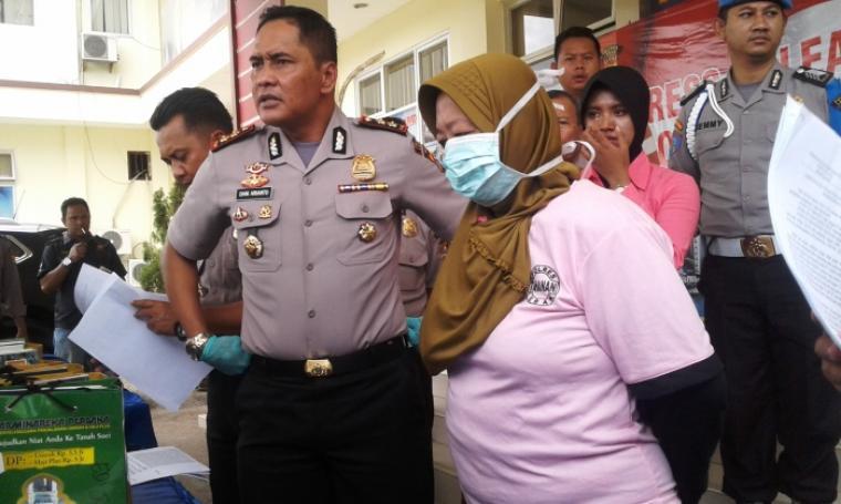 Ati Siti Fatimah tersangka penipuan dan penggelapan pemberangkatan Jamaah Umroh di Rangkasbitung saat digiring petugas. (Foto: TitikNOL)