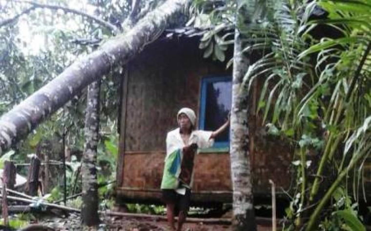 Seorang warga sedang berdiri di depan rumahnya yang tertimpa pohon. (Foto: TitikNOL)