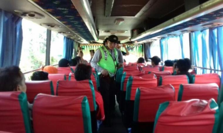 Petugas Polda Banten saat melakukan pemeriksaan di dalam bus, guna mencegah mobilisasi massa dari Banten ke Jakarta untuk mengikuti Tamasya Al-Maidah. (Foto: TitikNOL)
