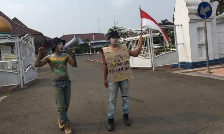 Dua mahasiswa yang tergabung dalam Himpunan Mahasiswa Indonesia (HMI) Cabang Serang, tengah melakukan aksi unjuk rasa di depan Kantor Bupati Serang. (Foto: TitikNOL)