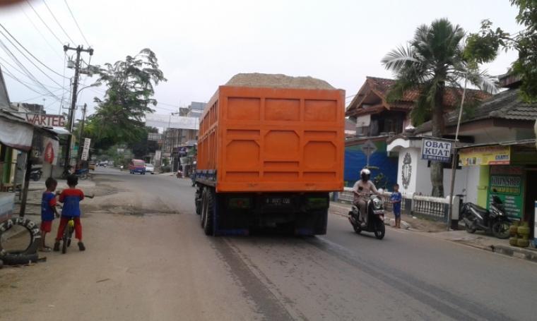 Kendaraan Dump Truk Pengangkut Pasir Basah dan Melebisi Tonase melintas di ruas jalan Ahmad Yani - Rangkasbitung. (Foto: TitikNOL)