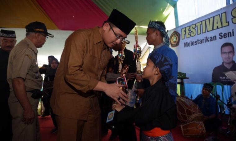 Wakil Gubernur Banten Andika Hazrumy saat menyerahkan piala kepada pemenang lomba Festival Seni Budaya Banten. (Foto: TitikNOL)