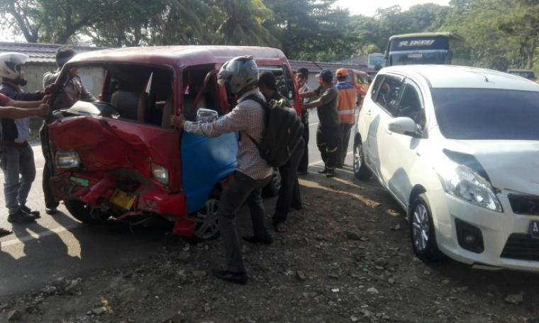 Petugas bersama warga ketika berusaha mengevakuasi angkot yang tabrakan dengan Suzuki Ertiga. (Foto: TitikNOL)