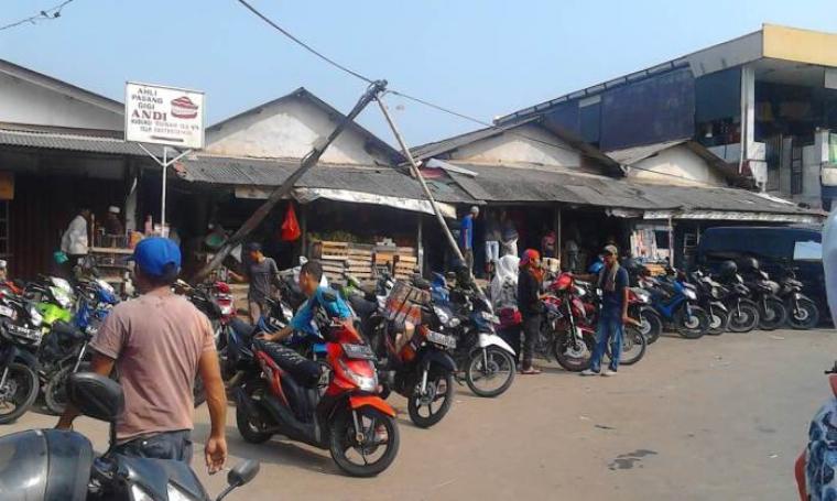 Tiang milik PT. Telkom di area pasar dan lahan parkir pasar Gajrug, Kecamatan Cipanas nyaris roboh dan mengancam keselamatan jiwa pengunjung pasar. (Foto: TitikNOL)
