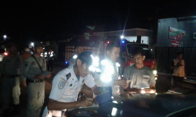 Petugas Tim Terpadu tengah memberhentikan dan melakukan penilangan terhadap truk angkutan pasir basah yang melebihi tonase di ruas jalan Rangkasbitung - Cimarga. (Foto: TitikNOL)
