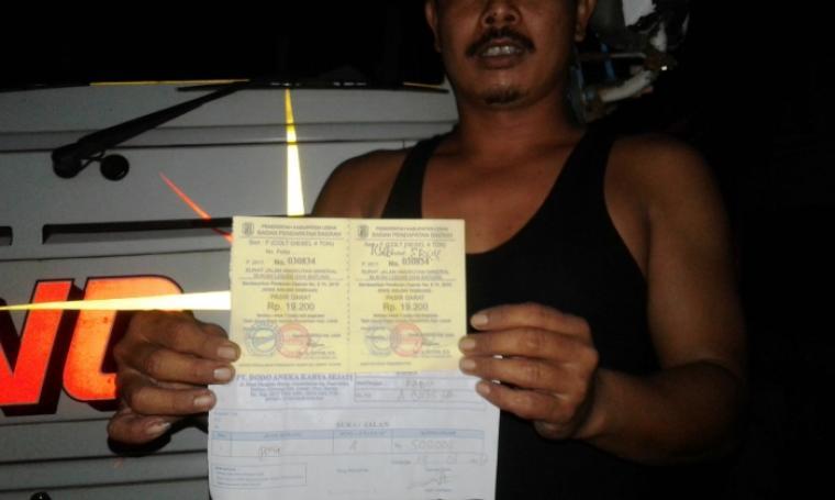 Jumri, salah seorang sopir truk saat menunjukan surat jalan yang dikeluarkan perusahaan tambang pasir PT. Dodo Aneka Karya Sejati. (Foto: TitikNOL)