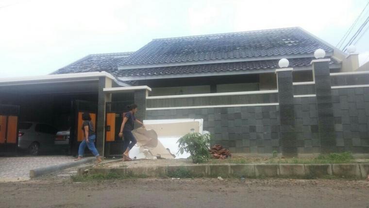 Dua orang pemilik rumah terlihat membereskan puing-puing usai meledak akibat kebocoran gas. (Foto:TitikNOL)